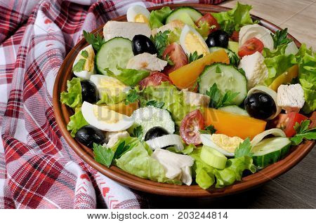 Vegetable salad with chicken and eggs olives in lettuce leaves. Horizontal shot. Close-up.
