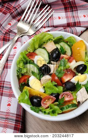 Vegetable salad with chicken and eggs olives in lettuce leaves. Vertically shot.
