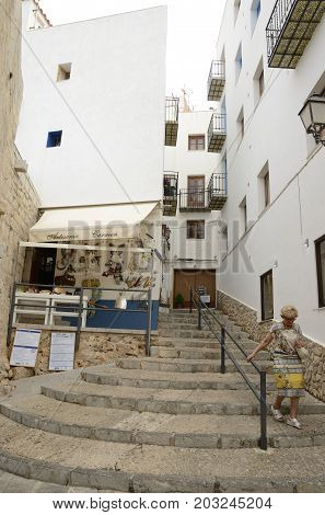 PENISCOLA, SPAIN - JULY 23, 2017: Woman going down by stairs at steep street in Peniscola Castellon Spain.