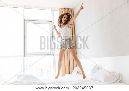 Full length portrait of a young casual woman in earphones listening to music and jumping on bed indoors