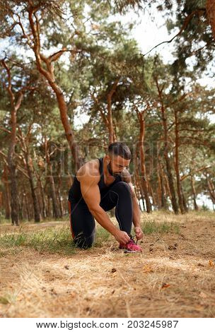 A photo of a bodybuilder on a running tying his shoelaces on a green forest background. A serious male runner tying his pink shoe before a run in the park. Sports, healthy, people and outdoors concept