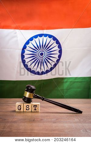 Stock photo of GST low in india. GST text  written over wooden blocks with wooden gavel over it and indian national flag or tricolour in the background, selective focus