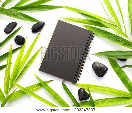 Bamboo leaf and black paper background. Black paper notebook mockup. Green bamboo leaf and beach pebbles flat lay. Blank notepad top view. Spa beauty banner template with text place. Bamboo decor
