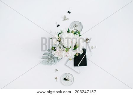 Flat lay home office desk. Female workspace with white peonies bouquet silver accessories black diary on white background. Top view feminine background.