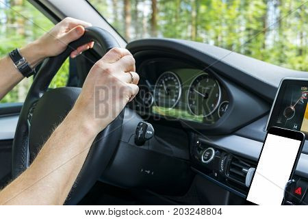 Male hands holding car steering wheel. Hands on steering wheel of a car driving near the lake. Man driving a car inside cabin. Smartphone in holder with isolated white empty blank screen. Copy space