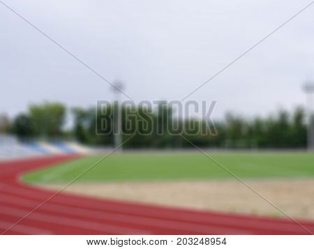 A blurred summer empty stadium with a football field and a red track for running trainings and competitions as a background. Sports, outdoors, summer, football concept. Copy space.