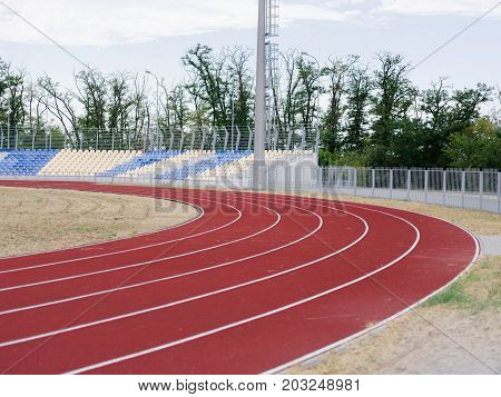 A summer red track for running trainings and competitions on a green natural background. Running track in the sports stadium. Sports, outdoors, summer concept. Copy space.