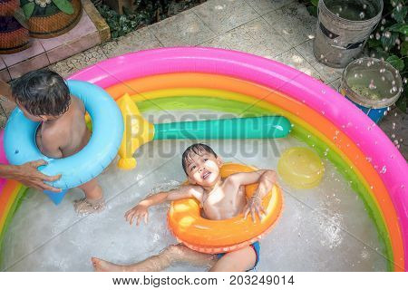 Top view of boy play water and turning face up in kiddie pool . Leisure activity