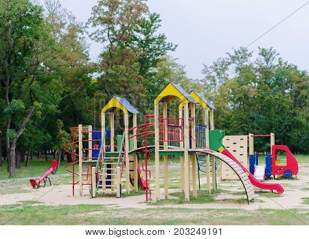 Bright playground on a natural background. A colorful playground equipment for children's active pastime in the park. Red slides. Outdoors, sports, childhood concept.