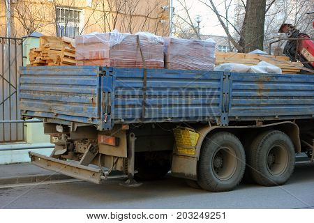 back of flatbed truck with side body loaded with building materials