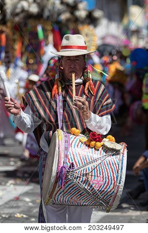 June 17 2017 Pujili Ecuador: man playing on flute and drum simultaneously walking the Corpus Christi parade