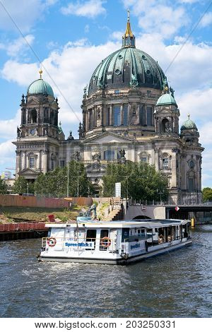 BERLIN, GERMANY - AUGUST 07, 2017: The Berlin Cathedral in the center of the city. In the foreground is a ship with passengers on the river Spree