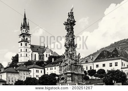 Saint Catherine's church with Plague column in Kremnica city Slovak republic. Architectural theme. Black and white photo.
