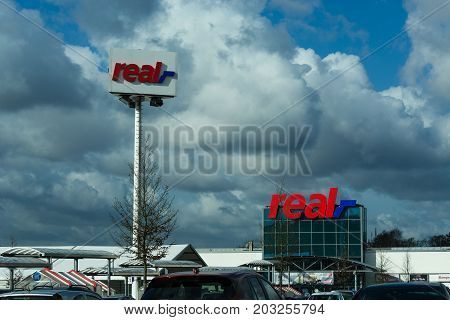 HEILIGENHAUS NRW GERMANY - FEBRUARY 24 2017: Real logo on department store in Heiligenhaus in front of a dramatic sky. Real Warehouse is a German trading chain.