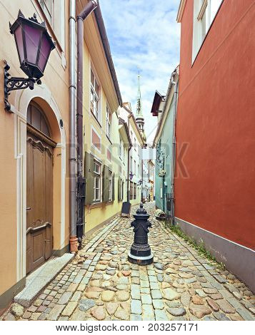 Narrow medieval street in old Riga city, Latvia. In old Riga city tourists can find a unique atmosphere of Middle Ages and famous ensembles of Gothic architecture