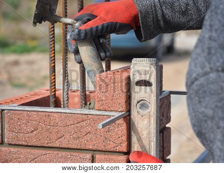 Bricklayer worker installing red blocks and caulking brick masonry joints exterior wall with trowel putty knife and fixing with spirit level outdoor