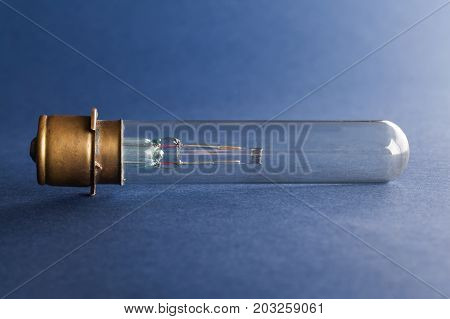 Vintage cinema lamp. Light bulb bronze surface on blue paper background, macro view shallow depth of field photo