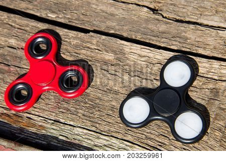 Two fidget spinners on rustic wooden table. Toy for stress relief
