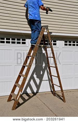 A man holding a drill stands for repair on a tall wooden step ladder