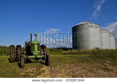 HAWLY, MINNESOTA, September 3, 2017: An old green John Deere 720  tractor parked alongside Butler Bins is a product of John Deere Co, an American corporation that manufactures agricultural, construction, forestry machinery, diesel engines, and drivetrains