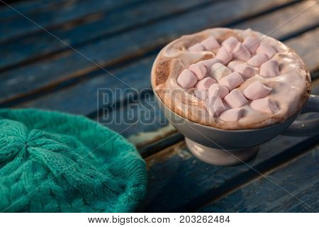 Close up of hot chocolate by cap on wooden table