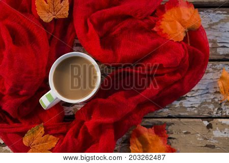 Overhead view of coffee cup amidst scarf on wooden table