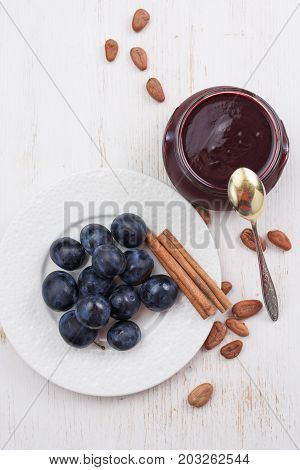 Homemade plum and chocolate jam served with fresh organic plums cinnamon sticks and raw cocoa beans on white table above view