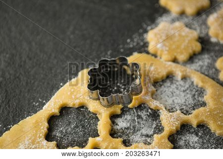 High angle view of flower shape mould on dough at table