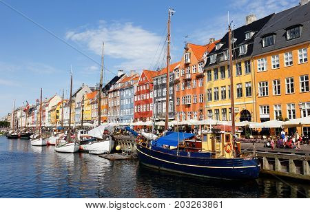 Copenhagen Denmark - August 24 2017: View of the tourist attraction area Nyhavn with restaurants and colorful buildings at the waterfront with old boats.