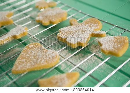 High angle view of powdered sugar on cookies over cooling rack at table