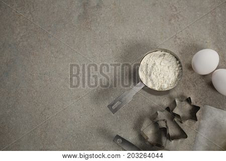 Overhead view of flour in measuring cup by moulds and egg on table