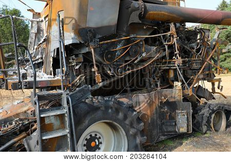 Closeup of a burnt out combine harvester in field