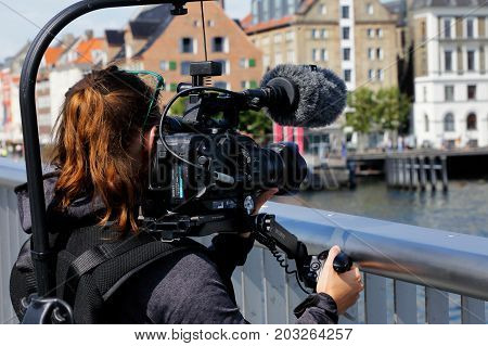 Copenhagen Denmark - August 24 2017: A female cameraman uses a stabilized professional video camera in Nyhavn.
