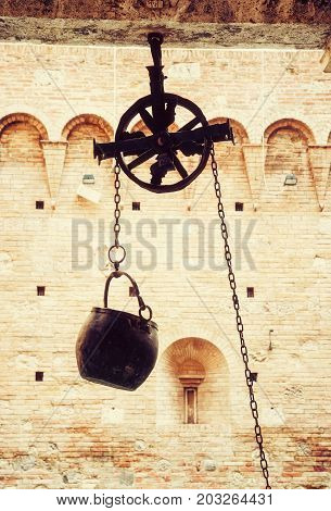 Metal bucket on a pulley hanging in the courtyard of the historic palace Siena Tuscany Italy. Photo filter.