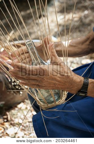 Basket maker creates a cover for a wine flask