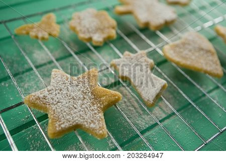 Powdered sugar on cookies over cooling rack at table