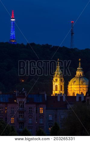Church of Saint Nicholas lightup with lighting lookout tower Petrin behind at evening in Prague.