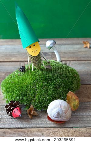 Funny pinecone gnome on a moss hill. Autumn toys from nature materials.