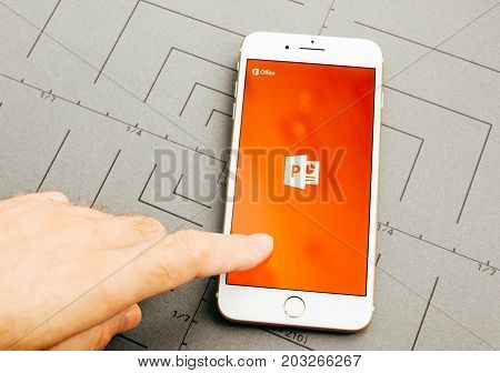 PARIS FRANCE - SEP 26 2016: Male hand holding New Apple iPhone 7 Plus after unboxing and testing by installing the app application software Power Point by microsoft