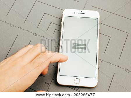 PARIS FRANCE - SEP 26 2016: Male hand holding New Apple iPhone 7 Plus after unboxing and testing by installing the app application software iTunes remote