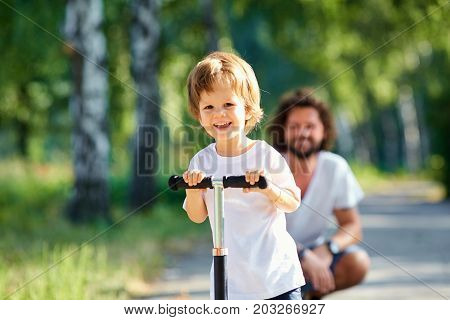 The boy skates on a scooter in the park with his father.