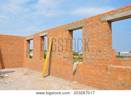 Interior of a unfinished red brick house under construction. Closeup on windows hole construction