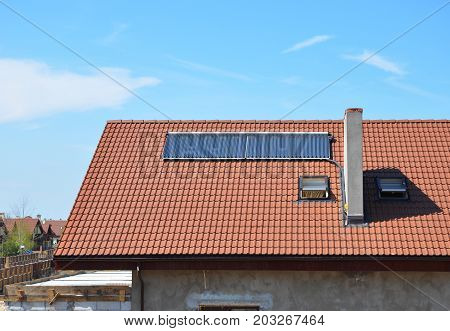 Energy Efficiency New Passive House Building Concept Exterior. Closeup on Solar Energy Water Panel Heating Solutions Dormers Skylights Ventilation Rain Gutter Skylights and Chimney Outdoor