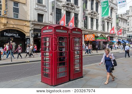 LONDON ENGLAND - JUNE 09 2017: Street view with pedestrians and telephone booths near London Trocadero and Piccadilly circus in London UK