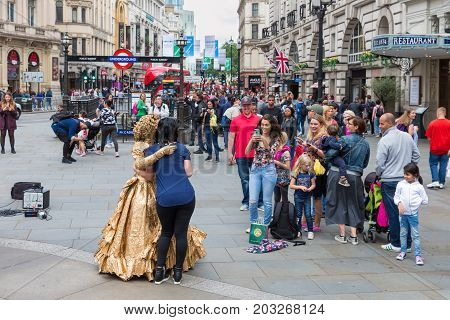 LONDON ENGLAND - JUNE 09 2017: Unknown people making pictures of living statue at Piccadilly Circus in London UK