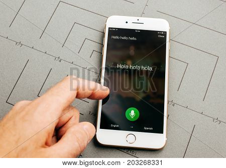 PARIS FRANCE - SEP 26 2016: Male hand holding New Apple iPhone 7 Plus after unboxing and testing by installing the app application software using Microsoft Translator with voice
