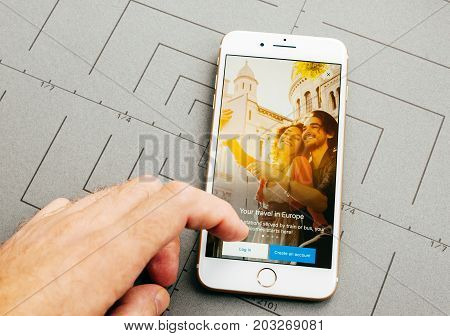 PARIS FRANCE - SEP 26 2016: Male hand holding New Apple iPhone 7 Plus after unboxing and testing by installing the app application software voyages sncf train travel app