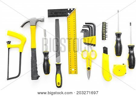 constructor desk with set of building implements with screwdriver on white desk background top view