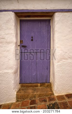 July 22, 2017 Barichara, Colombia: rustic colourful door on white colonial house one of the many attractions in the colonial town