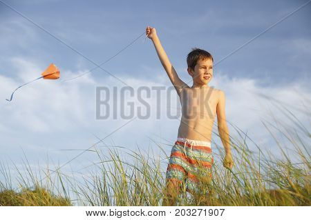 boy in the dunes on the beach playing with a kite. child holding a flying kite against the blue sky. Copy space for your text